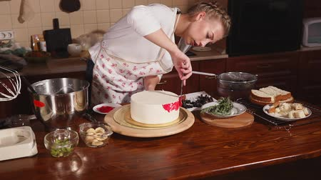 bıçak : Young and attractive pastry chef is applying pink glaze on a cake. She is bending over table with a knife.