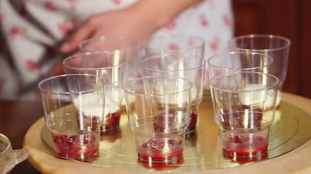 tiered : close up shot of the chefs hands, who puts the vanilla cream in plastic cups, the woman makes a dessert with fruit, the dishes stand on a wooden tray Stock Footage