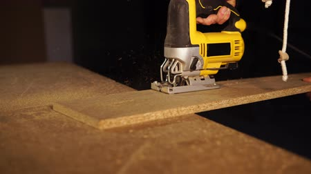 shaves : Close up shot of a skilled carpenter sawing piece of wood in a workshop. He is using an electric saw.