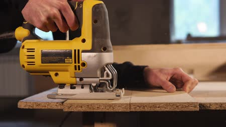 shaves : Side view shot of a professional carpenter using electric saw to deal with a wood boards. He is going along the drawn line.
