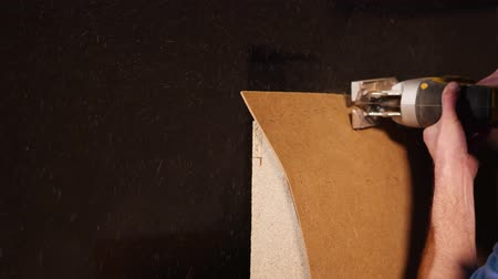 shaves : Close up shot of carpenter cutting excess parts of a plywood. He is using big electric saw in a workshop.