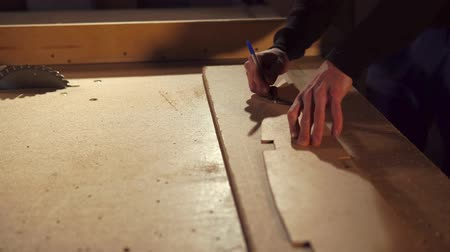 took : Working carpenter is drawing straight line on a piece of wood. He is tracing the shape of sample.