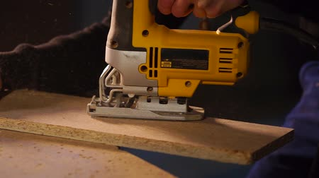 shaves : Close up shot of a qualified carpenter working with a electric saw in his workshop. He is carefully sawing wood board diagonally.