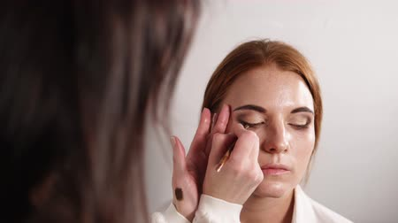 eyeshade : portrait of a young and beautiful woman, who makes make-up with a brush, a professional make-up artist applies cosmetics to the eyes of a lady, an artist uses dark shadows Stock Footage
