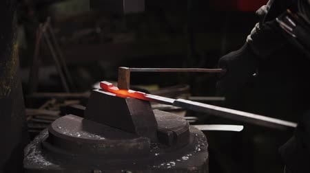 kowalstwo : close up shot of a blacksmiths hands, a man hits the hammer with a hammer over a hot piece of steel, which will then become a horseshoe, the person is in a blacksmith shop