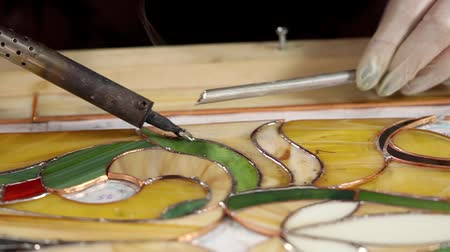 üveges : Stained glass master is holding soldering iron and solder over colored glass. Following the lines with solder. Stock mozgókép