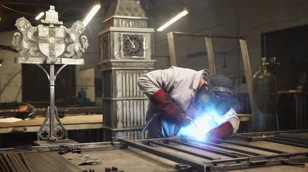 artsy : Professional welder is making art using metal bars in his workshop. Sparks are popping off the welding machine.