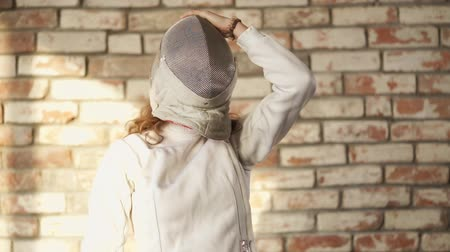 meç : Confident woman is wearing fencing mask for practice with partner. She is standing in studio against a brick wall.