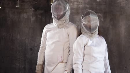 meç : Male and female fencers are posing together in studio against concrete wall. They are dressed in fencing uniform.