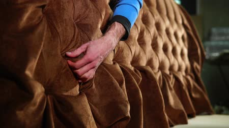 készítő : Worker is correcting folds in upholstery of the sofa. Exclusive soft furniture, producing for order in a craft workshop