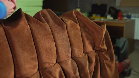 alaplap : Skilled workman is making a luxury sofa. He is wrapping a base by velvet cloth and creating a design of hand made furniture