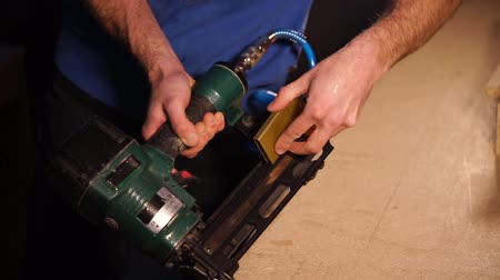 brackets : Cabinet maker is preparing a stapling machine for works. He is putting brackets inside a tool and closing it, holding in hands, close-up Stock Footage