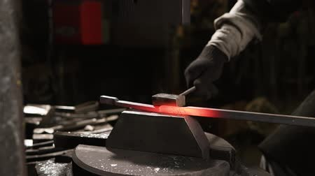 kowalstwo : Blacksmith is using hammer machine for shaping metal blank. He is holding beam on a small plate and automatic hammer is hitting on top Wideo