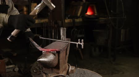 kowalstwo : Metalworker is processing red hot steel detail in forge. He is turning it and hitting by beater in dark workshop Wideo