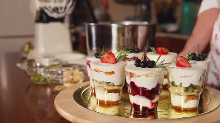 rowanberry : Exclusive sweets in restaurant are demonstrated on a bar. Close up of cups with bright fruits and white butter cream