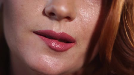 vöröshajú : Redhead girl is biting her lip and smiling. Close-up of her mouth, she is flirting with camera