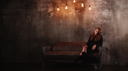 fetching : Redhead girl is crossing legs and posing, looking to camera. She is in a luxury leather couch, standing in a dark living room