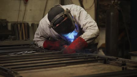 heat resistant : Man is wearing welding helmet and fireproof red gloves, conducting welding works. He is standing near workplace in a workshop Stock Footage