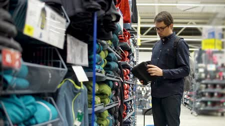 süet : Grown man in casual clothes and glasses choosing warm clothes in a sport shop. Taking different sweaters from shelves. Stok Video