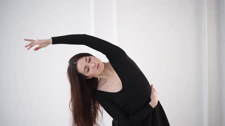 teljesen : Engaging brunette dancer is stretching in completely white studio wearing black. She is tilting to sides. Stock mozgókép