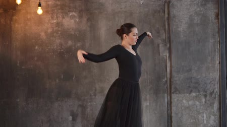 lem : an elegant lady in a black dress rehearsing ballet, she elegantly moves her hands to music, a woman moves from one ballet position to another