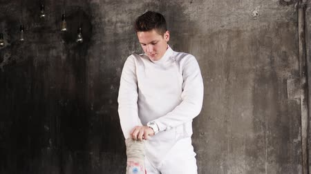 meç : Fencer is preparing for fight, pulling glove. He is standing near old wall, looking to a side and waiting, young sportsmans