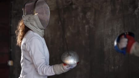 meç : Woman with fencing mask on her face is training in a hall. She is attacking with epee and protecting, close-up during practice session of fencers school Stok Video