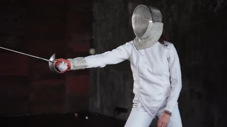 meç : Sportswoman with fencing mask on her head is attacking by sword. She is stepping forward and back, moving her epee, modern fencing discipline Stok Video