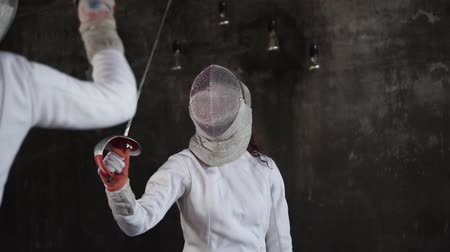 meç : Pupils are practicing impacts in a fencing. Sports girl is in a mask is attacking, epees are crossing during fight Stok Video