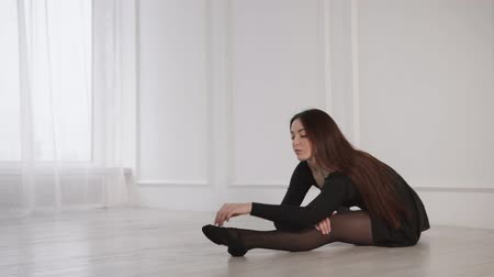 külotlu çorap : Ballerina is stretching on a floor in a light hall in dancing school. She is sitting and tensing her muscles before class, back view