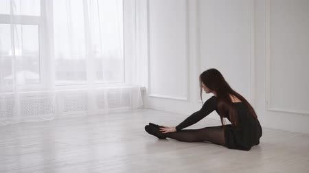 külotlu çorap : Modern ballerina is warming up before training in a light hall. Talanted and skilled girl is prepairing for performance on a scene Stok Video