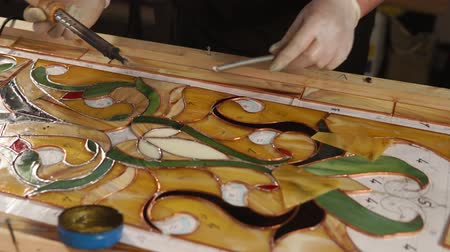 glass master : Skilled workman is processing copper tape of stained-glass panel. He is using tin solder and soldering iron, assembling and fixing beautiful hand made stained-glass Stock Footage