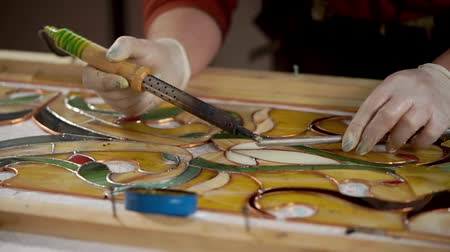 színezett : Master is using a soldering iron for decorating and processing frame of stained-glass picture. He is melting tin and applying it on copper base.