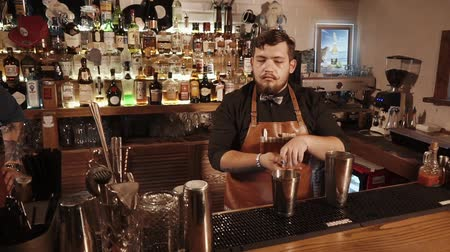 imitace : ROSA KHUTOR - FEBRUARY 2018: BAR Handsome bartender adding some syrup in a metal shaker on bar counter. Mixing drinks in a shaker standing behind the bar. Serious face. Dostupné videozáznamy