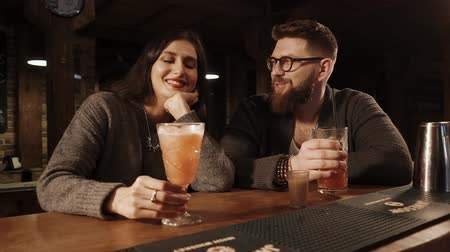 drinking coffee : ROSA KHUTOR - FEBRUARY 2018: BAR Portrait of two lovers enjoying their evening at the bar. Drinking exotical cocktails leaning on a wooden bar counter. Stock Footage