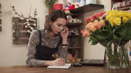 jak : a young and pretty woman works as a florist in a flower shop, a lady holds a smartphone in her hand and talks to her client, a flower business master stands near a laptop and roses in a vase