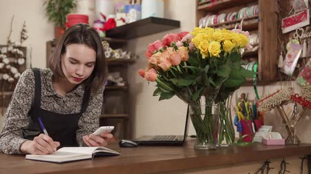 cinta de regalo : a young and pretty woman works as a florist, a lady holds a phone in her hand and records orders for bouquets in a notepad for recording Archivo de Video