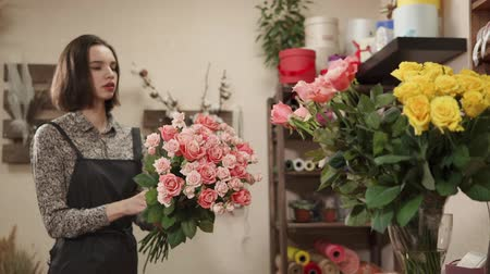 obra prima : a young woman who looks like a student, makes a bouquet of pink roses, the lady collects a floral compassion on her workplace in a floral masterpiece