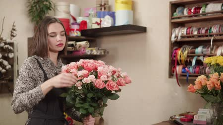 cheirando : a young woman sniffing flowers and enjoying their smell, a young florist enjoys the flower arrangement in the workshop where she works