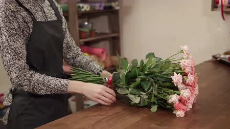 employed : Close up shot of a womans hands derocating a beautiful bouquet of roses. She is tying knot on it indoor.
