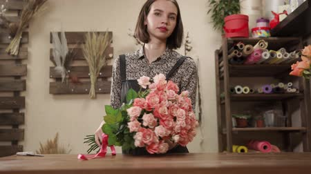 designing : Young beautiful female florist decorating pink roses bouquet indoor. She is tying a red ribbon to it. Stock Footage