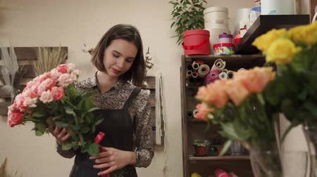demonstrar : a young florist holds a bouquet of roses in her hands, a lady gathered a bouquet in a flower shop, she adjusts the pink ribbon that decorates the flowers Vídeos