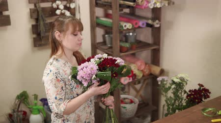 estação de trabalho : a young woman holds a bouquet of chrysanthemums and green leaves in her hand, a florist collects a flower arrangement in a flower stall, this is her small business