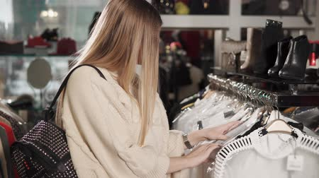 vállfa : a young and pretty woman wants to buy fashionable clothes, a stylist with a backpack on her back examines clothes on a hanger, a lady is in an expensive boutique