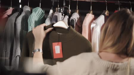 восхищенный : a young woman holds a warm sweater on her hanger, on which a tag with a price weighs, a lady looks at the material from which this clothing is made Стоковые видеозаписи