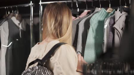 покупатель : a young and pretty woman wants to buy clothes, the lady tries to update her wardrobe, she carefully studies the assortment on the hangers proposed by the store Стоковые видеозаписи