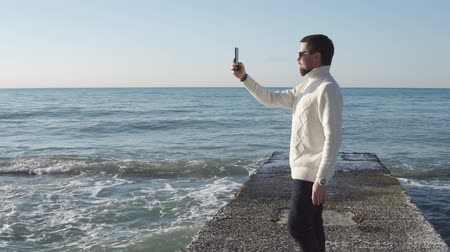 hayran olmak : Young man in sunglasses is taking photo and video on his modern mobile. He is placing on a concrete pier in sunny day, sea waves are crushing on edges