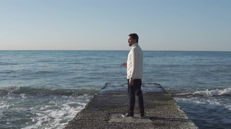 hayran olmak : Inspired man is enjoying beautiful ocean landscape in clear summer day. He is gone on pearce in seawater and looking on sides under sunshine Stok Video