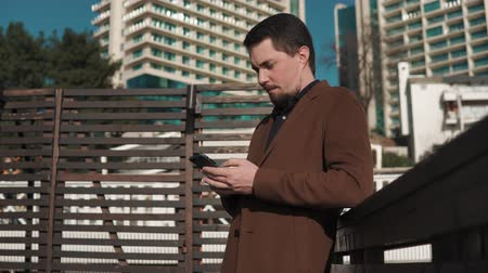 cityspace : a young and handsome man dressed warmly, he stands outside in the city space and holds a smartphone in his hand, a man prints text sms on the screen of a fashionable gadget Stock Footage