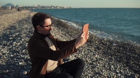 notizblock : Handsome man is sitting on a coast of sea in evening and using tablet. He is saying hello and showing panorama for his interlocutor on a video call